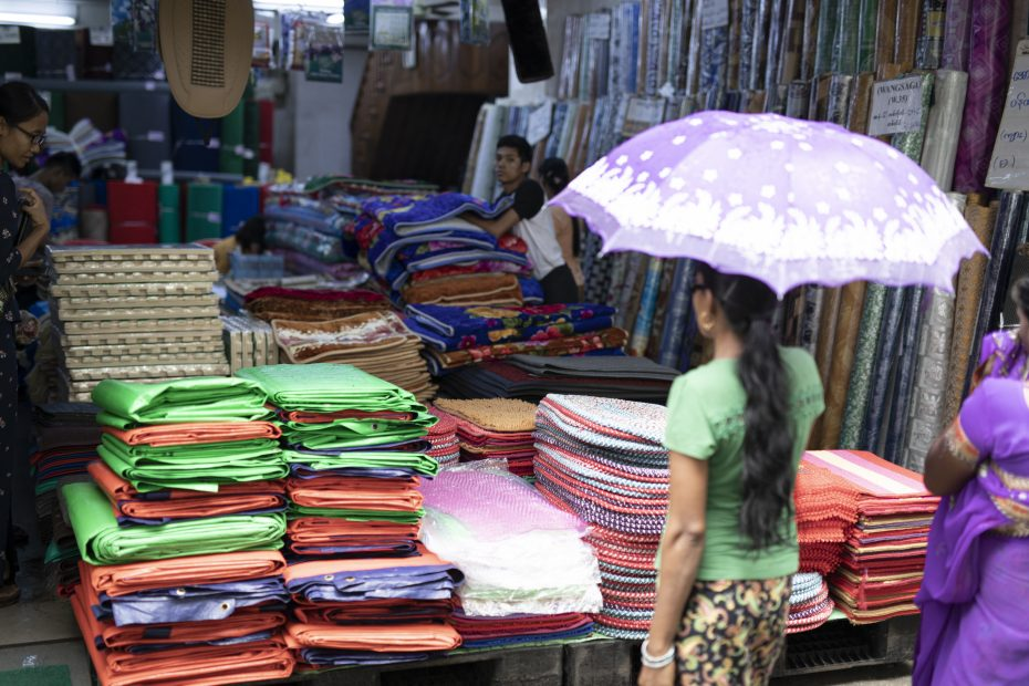 A woman stands in front of a market stall with an umbrella